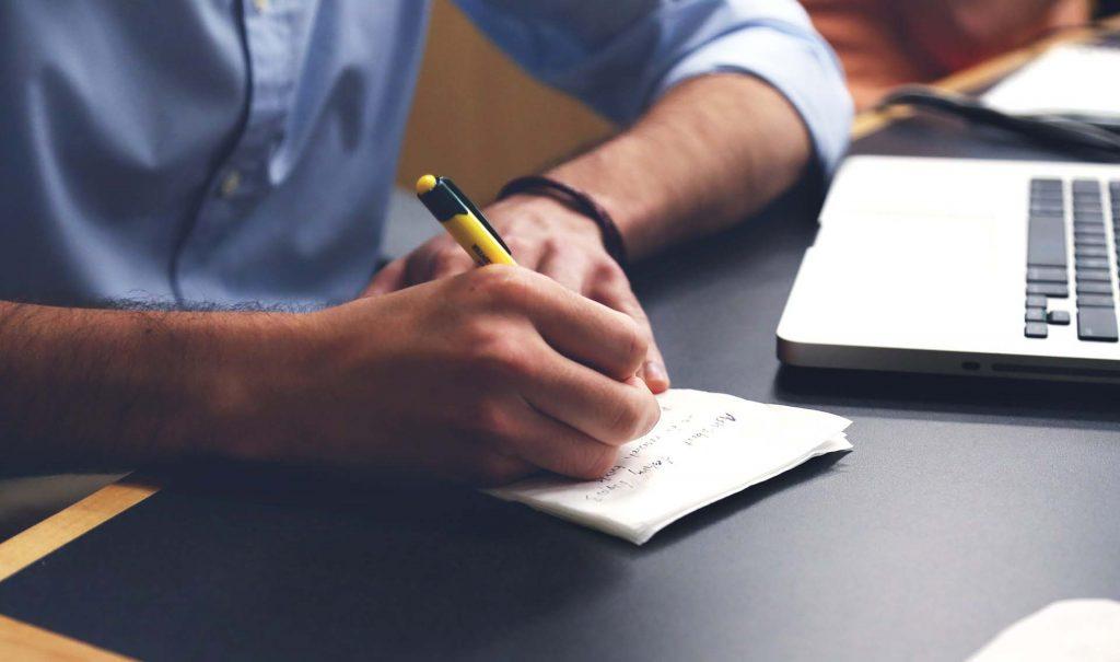 homme écrit sur un bureau